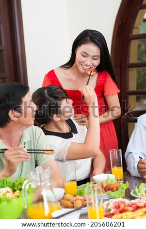 Girl feeding her mother with a piece of strawberry during the family dinner