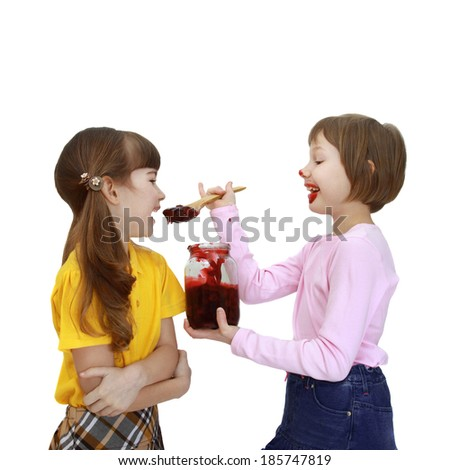 Girl feeds girlfriend of jam using big wooden spoon isolated on white background - stock photo