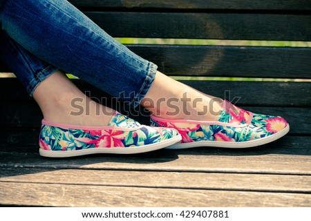 girl feet in lightweight summer shoes on wooden bench - stock photo