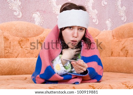 girl fell ill and lay on the couch with a thermometer - stock photo
