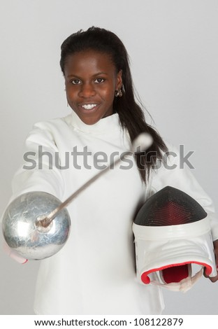 Girl fencer athlete with sword and mask over grey background - stock photo