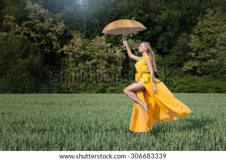Girl flies over the field. In her hands she holds an umbrella. - stock photo