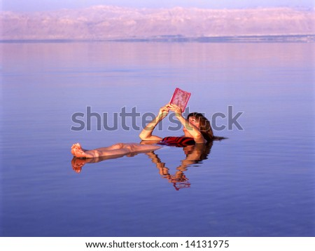 Girl floating at the Dead Sea, Jordan while reading a book - stock photo