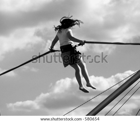 Girl flying high on a bungee trampoline (black & white) - stock photo