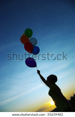 Girl flying with balloons at sunset - stock photo