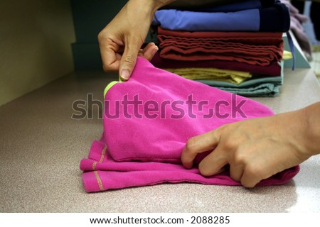 Girl folding laundry - stock photo