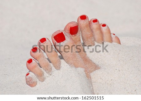 Girl foot in sand on the beach - red nails - stock photo