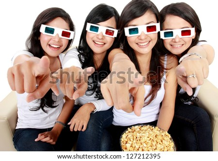 girl friends sitting on couch watching movie in 3d. pointing to the camera - stock photo