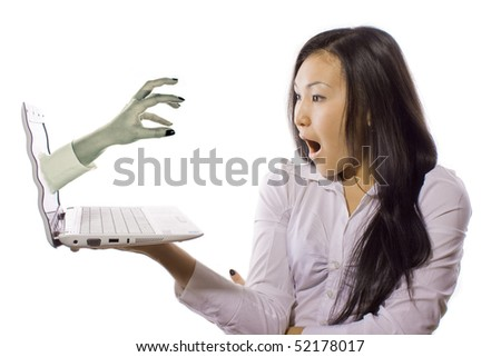 girl frightened of a hand from the laptop - stock photo