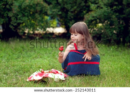 Girl gathers strawberries - stock photo