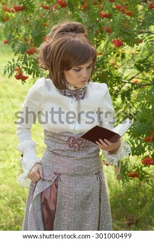 Girl gets angry while reading book. She wears retro style clothes.                                - stock photo