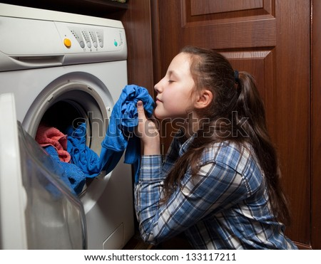 girl gets out of the washing machine clothes blue - stock photo