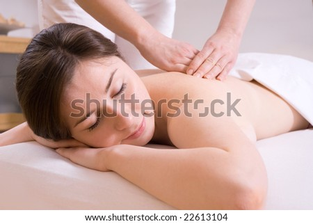 girl getting a back massage in the spa salon - stock photo