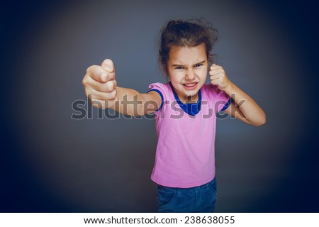 girl getting angry fist shows on a gray background cross process - stock photo