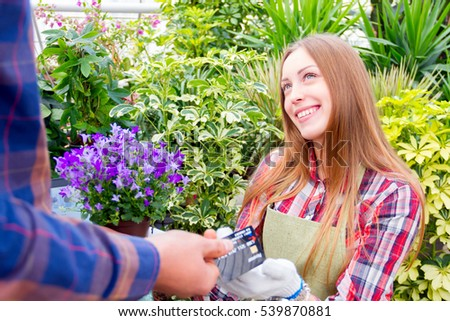 Girl giving a pot of purple flowers to the customer and taking a credit card.