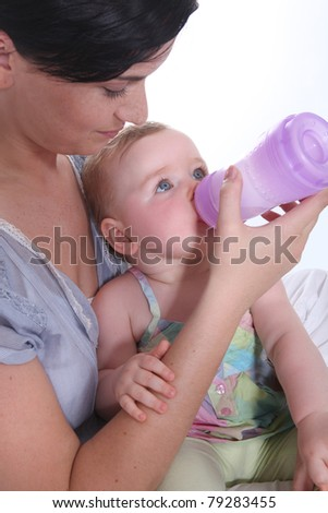 Girl giving baby her bottle - stock photo
