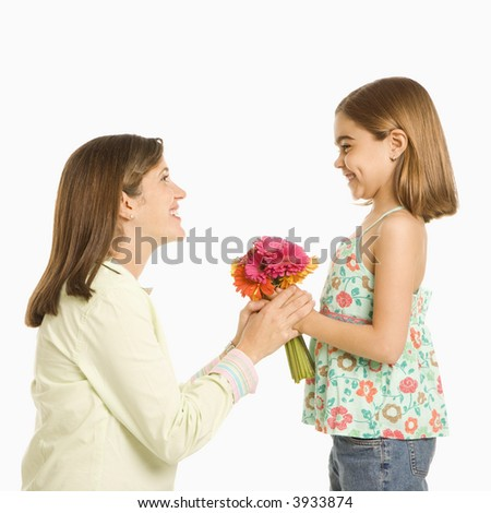 Girl giving bouquet of flowers to mother. - stock photo