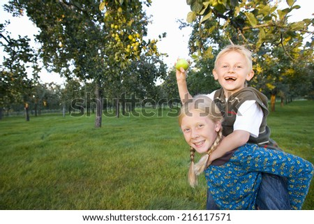 Girl (11-13) giving brother piggy back, boy with apple, smiling, portrait