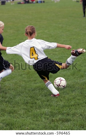 Girl giving it her all during a soccer game.  She is just getting ready to kick the ball as her opponent moves in. - stock photo