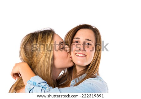 Girl giving kiss at her sister over white background