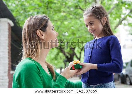 Girl giving to her mother a christmas present - stock photo