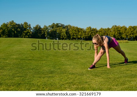 Girl go in for sport on the street. Fitness outdoors. Trainer show sports exercise on green meadow.