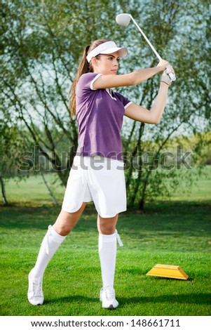 Girl golf player hitting ball on golf course