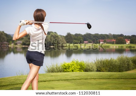 Girl golf player teeing-off from tee-box with driver, view from behind. - stock photo