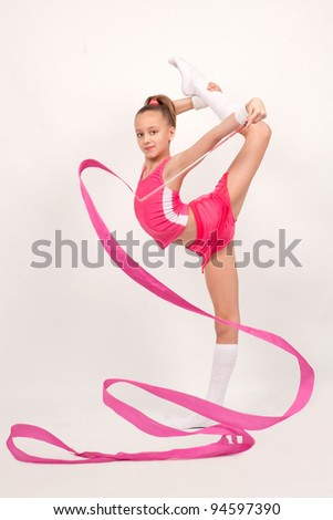girl gymnast does an exercise with ribbon standing on one leg - stock photo