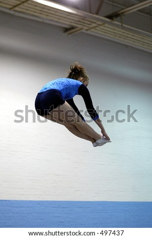 girl gymnast pike jump on trampoline wearing a blue and black leotard - stock photo