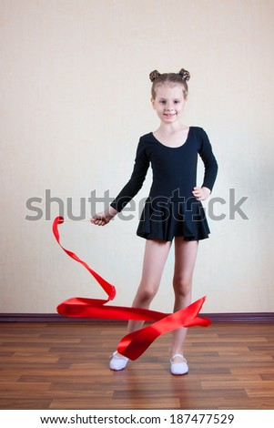 Girl gymnast with red ribbon - stock photo