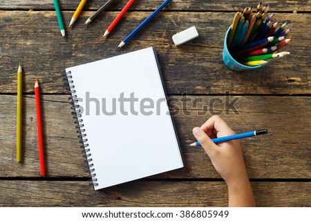 Girl hand drawing, blank paper and colorful pencils on old wooden table - stock photo