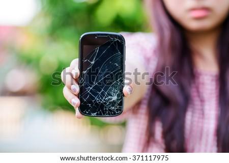 Girl hand holding cracked mobile smartphone - stock photo