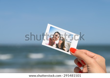 Girl Hand Holding Instant Photo Of Young Happy Couple, focus on hand