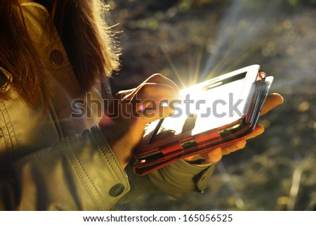 Girl hand touching screen on modern tablet. - stock photo