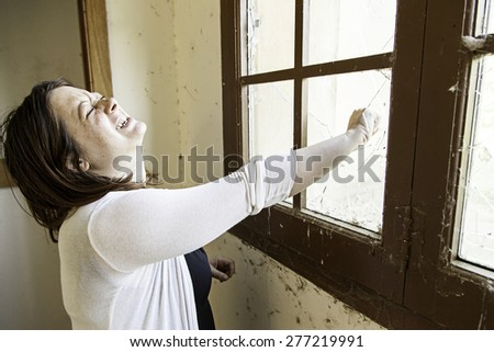 Girl hand window breaking, pain and fear - stock photo