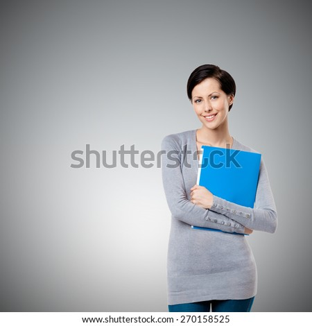Girl hands books and magazines, isolated on grey - stock photo