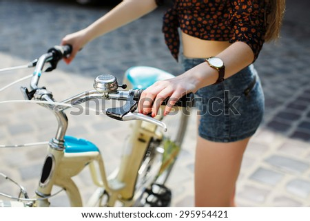 Girl hands holding a bicycle handlebar. Close-up. Outdoors.  - stock photo