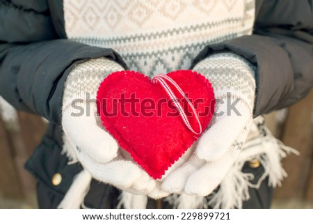 Girl hands in white knitted mittens holding romantic red heart. With love. St. Valentine concept. - stock photo
