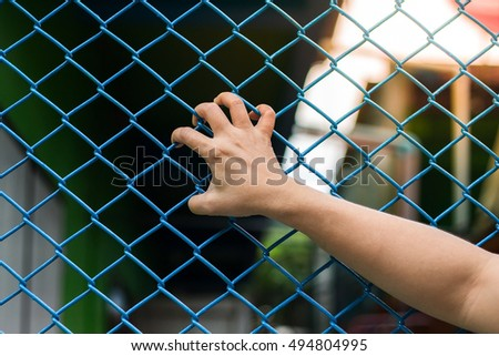 Girl hands on the wire fence,freedom concept