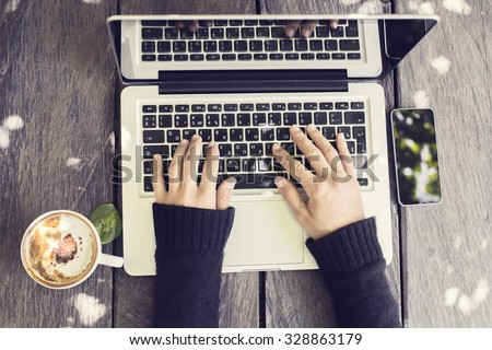 girl hands with cup of coffee, smartphone and laptop on a wooden table - stock photo