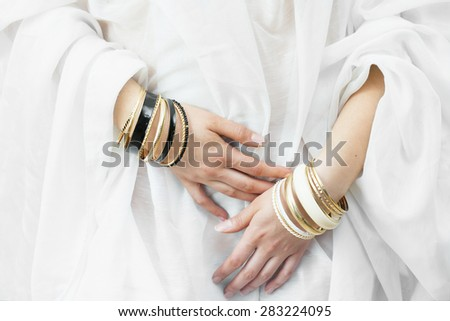 Girl hands with golden bracelets on a white cloth  - stock photo