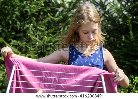 girl hanging laundry in the garden