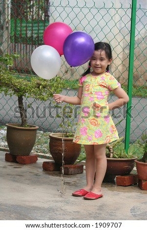 Girl happily holding colorful balloons - stock photo