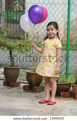 Girl happily holdings colorful balloons - stock photo