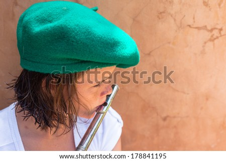 Girl Hat Music Mouth Organ Teen girl unidentified wearing green beret hat plays practices with wind flute instrument. - stock photo