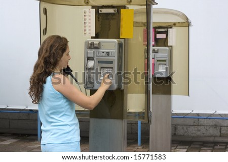 Girl having a call on a public telephone - stock photo