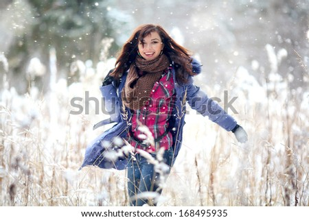 Girl having fun and jumping in the snow - stock photo