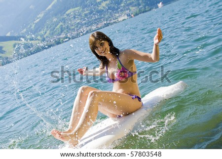 Girl having fun and relaxing on surfboard at the lake of Zell am See, Austria - stock photo
