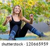 Girl having fun exercising outdoors on her mat on the grass laughing and smiling at the camera as she finishes an exercise - stock photo
